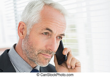 Businessman peeking through blinds while on call - Serious ...