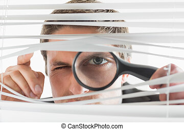 Businessman peeking through blinds with magnifying glass - ...