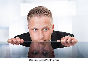 Businessman peering furtively over the top of his desk as he spies on a colleague or tries to remain out of the firing line to avoid any blame for a problem isolated on white
