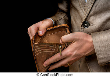 Businessman person holding an empty wallet isolated on black