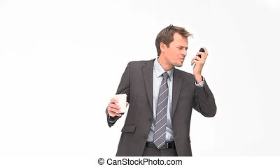 Businessman phoning while drinking coffee
