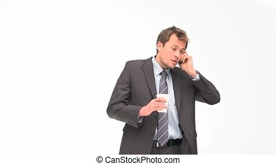 Businessman phoning while he is drinking coffee