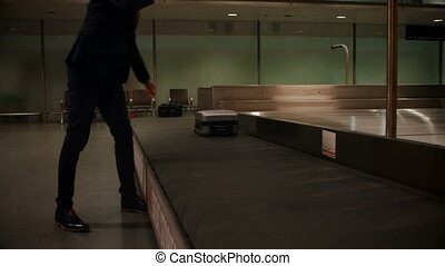 Businessman picking his luggage from baggage claim area 4k -...