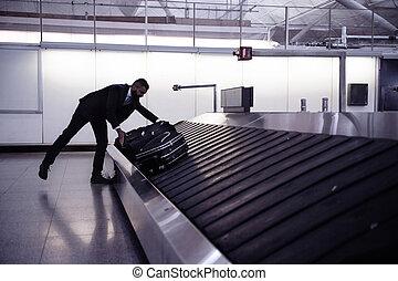 Businessman picking up suitcase on luggage conveyor belt, airport