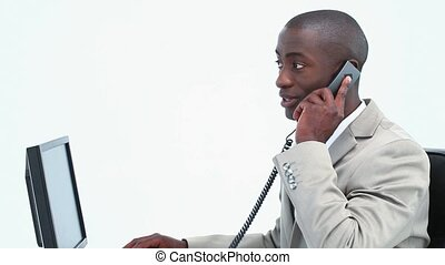 Businessman picking up the phone sitting at his desk against...