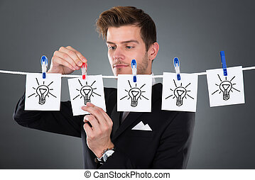 Young businessman pinning papers lightbulbs on clothesline against gray background