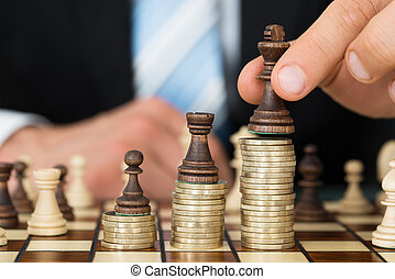 Businessman Placing Chess Pieces On Stacked Coins -...