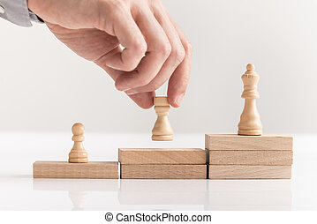 Businessman placing chess pieces on wooden blocks