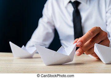 Businessman placing paper made origami boat on wooden desk