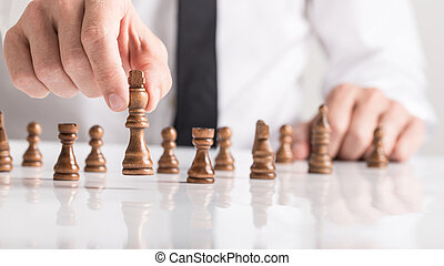 Businessman playing a game of chess on white table in a close up view of his hand
