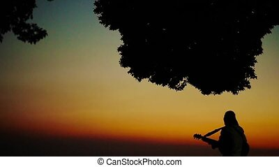 Businessman playing the guitar and singing on a hill silhouetted against a romantic city landscape