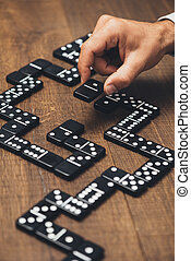 Businessman playing with dominoes and holding a tile, ...