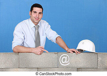 businessman pointing at an at sign on a wall