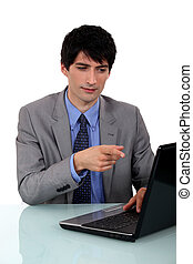 Businessman pointing at laptop screen