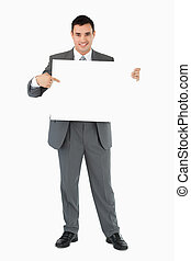 Businessman pointing at sign he is holding against a white...
