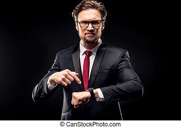 Businessman pointing at wristwatch