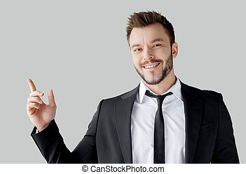 Businessman pointing copy space. Portrait of cheerful young man in formalwear pointing away and smiling while standing against grey background