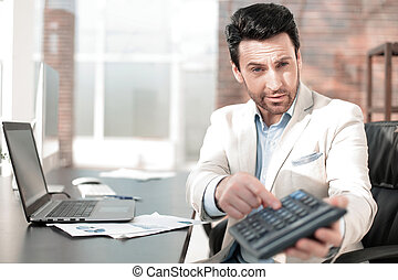 Businessman pointing to calculator in hand.
