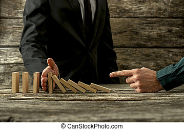Businessman pointing to falling dominos and his partner stopping them