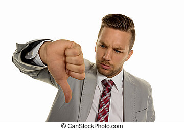 businessman pointing with thumbs down - a young entrepreneur...