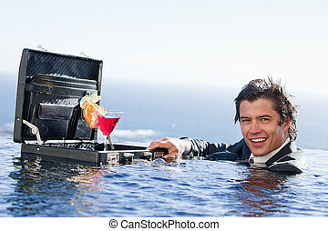 Businessman posing with a cocktail in a briefcase