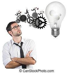 Businessman powering a big idea with a gear system