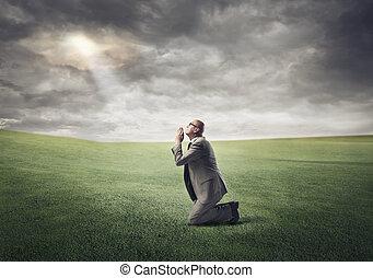 Businessman praying and kneeling