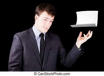 Businessman presenting a blank sheet of paper with room for text isolated on black