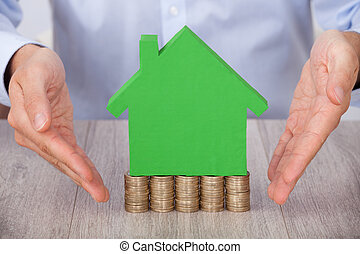 Businessman Presenting Green Model House On Stacked Coins