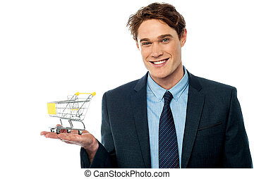 Businessman presenting shopping cart