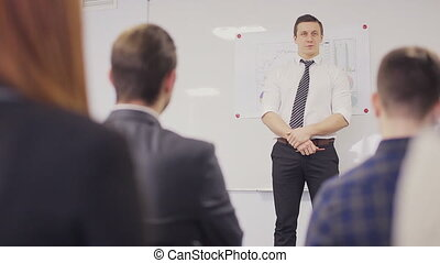 Businessman presenting to the team taking notes in the boardroom. Static shot