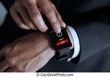 Businessman press button startup on smart watch in hand, dark background