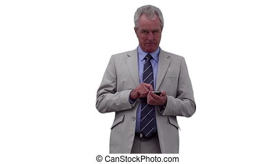 Businessman pressing buttons on his phone before looking around him