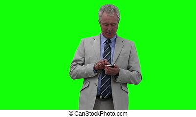 Businessman pressing buttons on his phone while looking around him
