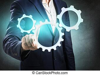 Businessman pressing on group of digital cogwheels. Harmonious work concept.