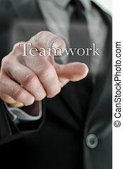 Businessman pressing Teamwork icon on a virtual screen