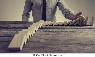 Businessman preventing dominoes from crumbling with palm on an old wooden table, retro effect faded look.