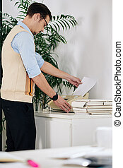 Young businessman in glasses printing out important document or report or sending fax