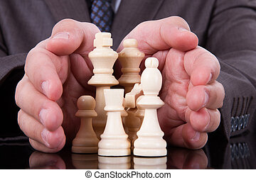 Businessman Protecting Chess Pieces