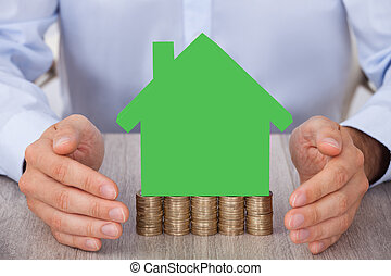 Businessman Protecting Green Model House On Stacked Coins