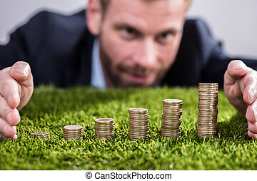 Businessman Protecting Stacked Coins On Grass
