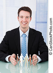 Businessman Protecting Team Of Paper People At Desk