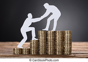 Businessman Pulling Colleague While Standing On Stacked Coins