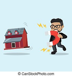 businessman pulling miniature house with magnet