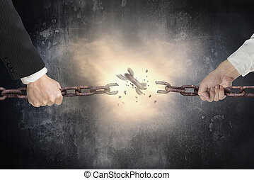 Businessman pulling rusty iron chains broken with red bright spark light on dark mottled concrete wall background, tug of war, business competitive concept