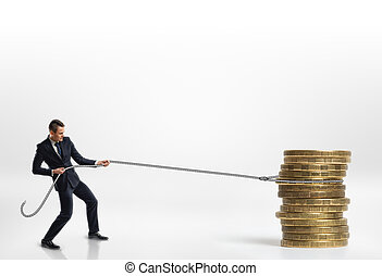 Businessman pulling stack of big golden coins with a rope isolated on white background