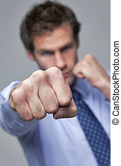 Businessman punching towards camera