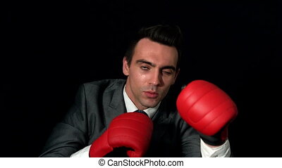 Businessman punching with red gloves on black background in...