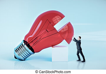 Businessman pushes a big red light bulb.