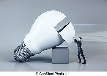 Businessman pushes a big white light bulb